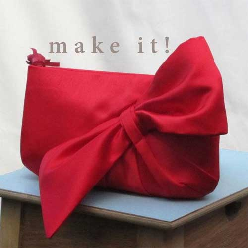 This clutch purse features a bow embellishment on the front that is integrated into the body of the front panel and gathers up to form the bow.