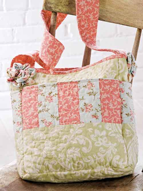 Ruched flower accents add the perfect finishing touch to this pretty patchwork bag.